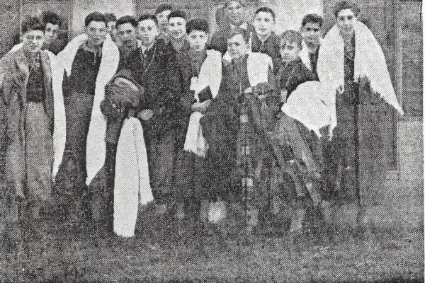 "A newspaper clipping titled, ""Dovercourt: The first batch of Jewish refugee children arrived at Parkeston from Germany early on Friday morning. Here is a group of boys outside one of the chalets in which they will live"""